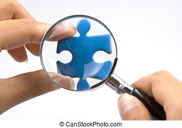 Magnifying Jigsaw Puzzle - Hands with magnifier over a piece...