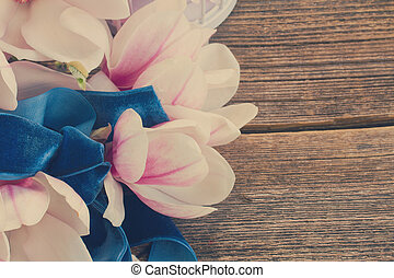 magnolia flowers with pearls on wooden table - magnolia...
