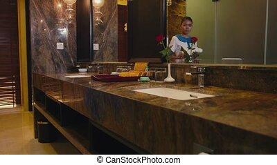 Maid cleaning hotel bathroom, job - Asian housekeeper...