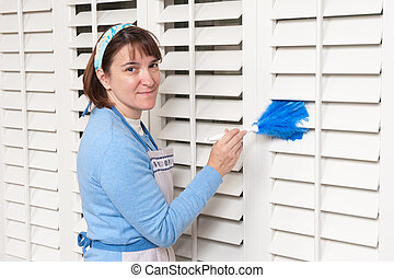 Maid cleaning shutters - A woman uses a feather duster to...