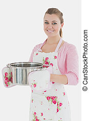Maid in apron holding kitchen utensil