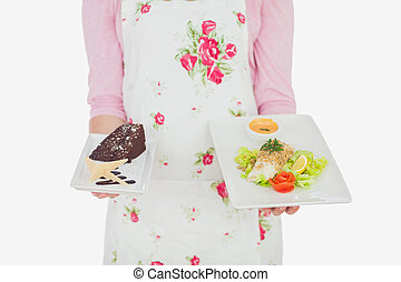 Maid in apron holding plates of pastry and meal