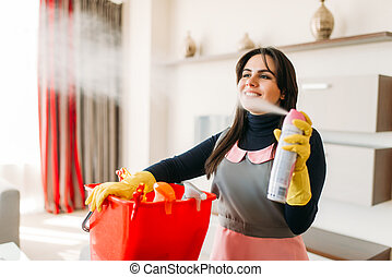 Smiling maid in uniform and rubber gloves sprays air freshener in hotel room. Professional housekeeping equipment, charwoman