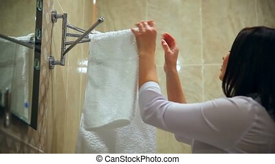 Maid makes staff woman cleaning bathroom towel straightens -...