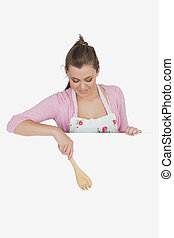 Maid pointing with wooden spoon on billboard