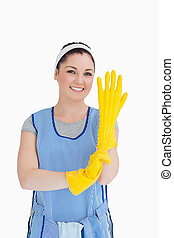 Maid putting on yellow gloves