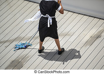 Maid with mop and in uniform cleaning floor