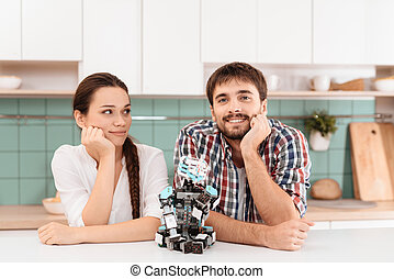 maigre, robot, kitchen., suivant, sourire., poser, ils, ils., type, assied, table., girl