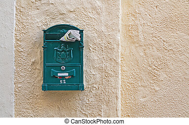 green mail box with a magazine stuck in it