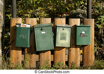 A row of mail boxes on a picket wooden fence.