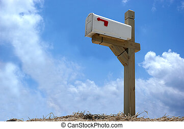 A mailbox mounted on wood stand in clear blue sky background