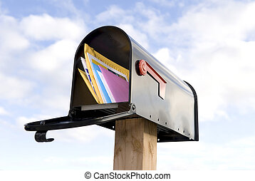 Mailbox and mail - A mailbox full of mail against a blue and...