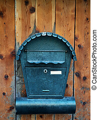 Mailbox for newspapers and letters on a wooden door