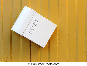 Mailbox - The white mailbox hanging awry on a yellow painted...