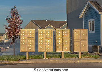 Mailboxes at the side of a road against houses and blue sky on a sunny day