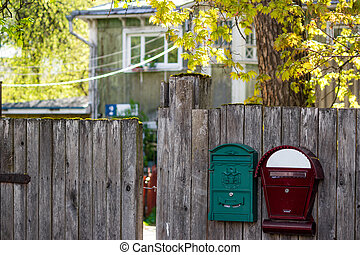 Mailboxes on the fence of a private house in the countryside, a cozy suburban area