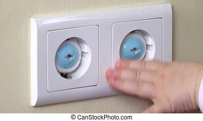 main bébé, atteindre, une, sortie électrique, couvert, à, bleu, prises sûreté