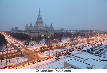 Main building of Moscow State University at night winter in Moscow, Russia, view through window