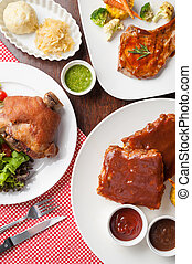 Top view of main course set including pork knuckle, pork chop, and barbecue ribs steak on wood table in restaurant