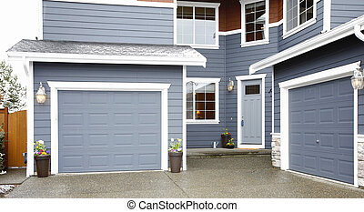 Main entrance of grey two story tall house exterior.