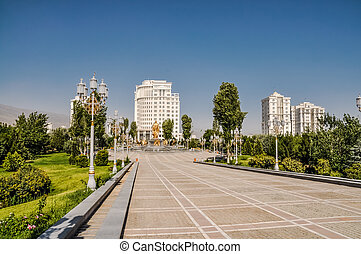 Photo of main square with golden statues surrounded by greenery and buildings of Ashgabat in Turkmenistan.