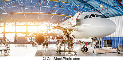 Maintenance and repair of aircraft in the aviation hangar of the airport, view of a wide panorama.