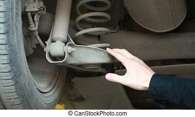 Maintenance car. man inspects a car shock absorbers
