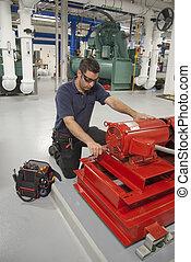 maintenance contractor repairing electric motor in industrial power complex