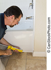 Maintenance Man - Contractor sealing tub base to keep water ...