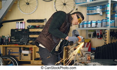 Maintenance man is using electric circular saw while working in his small workplace. Young man is wearing protective glasses and gloves and is listening to music with earphones.