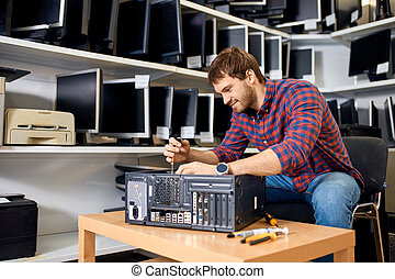 maintenance of system unit. handsome cheerful man learning to repair computer