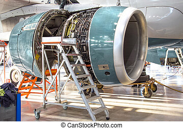 Maintenance, opened aircraft engine in the hangar in huge industrial hall