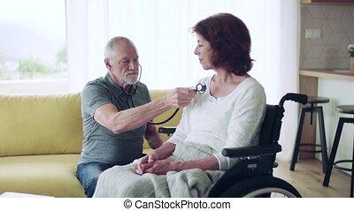 maison, fauteuil roulant, femme aînée, visiteur, pendant, ...