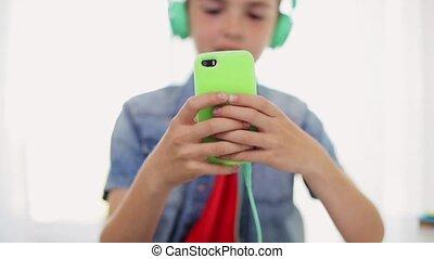 maison, garçon, smartphone, heureux, écouteurs