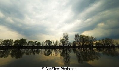 Majestic river landscape under setting sun sky with clouds. Overcast sky before storm. Volga River near Astrakhan, Russia