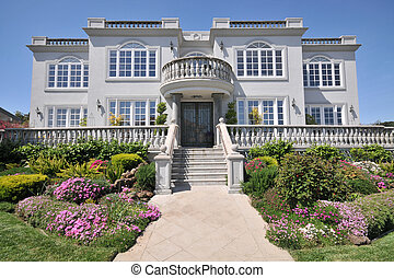 Majestic two story mansion with shrubs in yard. Blue sky....