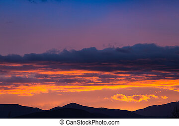 Majestic vivid sunset/sunrise with clouds over dark mountains silhouettes