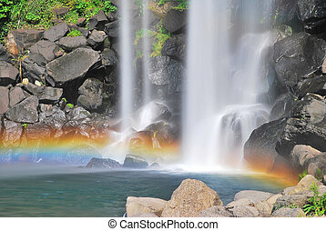 Majestic waterfall accentuated with a beautiful rainbow. Suitable for concepts such as zen meditation, serenity, environment, conservation of the earth, strength and power, and travel and vacation. Taken on Jeju island, Korea.
