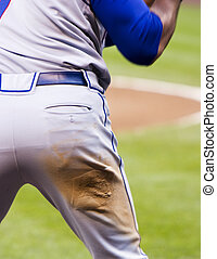 A major league baseball posterior on display while warning up before the batter took his turn at the plate. The dirt on the torn uniform pants were the result of a slide earlier in the game.