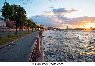 Makarova embankment, in the evening at sunset with the bright sun on the horizon . Saint-Petersburg.