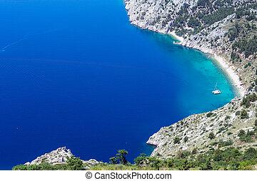 Makarska Riviera coast summer view with beach, azure water surface and sailing yacht (Croatia)