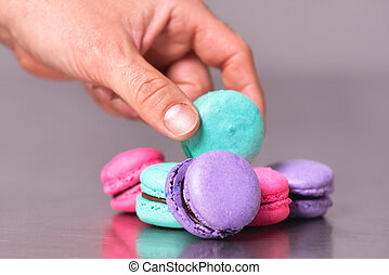 Make hand picking up a macaron the table