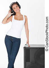 Make it louder! Beautiful young woman in headphones listening to the music while leaning on the speaker