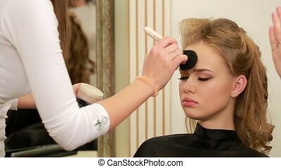 Make up applying. Face powder, facial makeup. Rouging young attractive girl's cheeks by makeup artist. Beauty woman making make-up with brush, Powdering skin