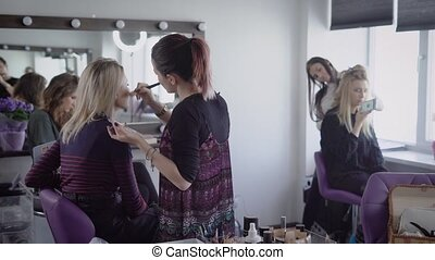 Make-up artist and hairdresser of famous beauty shop are working in tandem with two models preparing for future shooting. One master is applying cosmetics on client's face, another expert is finishing hairdo.