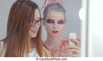 Make up artist and her client with creative unusual make-up...