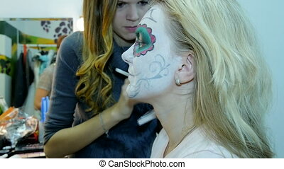 Make-up artist and stylist doing makeup model for Halloween.