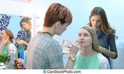 Make-up artist and stylist doing makeup model for photography