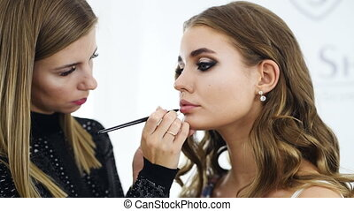 Make-up artist applies lipstick on amazing fashion model...