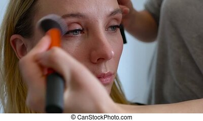 make-up artist applies powder and makes the correction of...